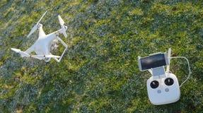 Bourdon blanc de quadcopter avec le contrôleur à distance au-dessus d'une herbe verte Photos stock