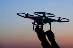 Bourdon de vol avec l'appareil-photo sur le ciel au coucher du soleil Photo stock