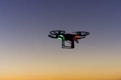 Bourdon de vol avec l'appareil-photo sur le ciel au coucher du soleil Photos libres de droits