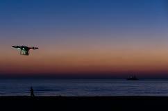 Bourdon de vol avec l'appareil-photo sur le ciel au coucher du soleil Photos stock