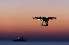 Bourdon de vol avec l'appareil-photo sur le ciel au coucher du soleil Image libre de droits