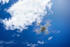 bourdon de vol avec l'appareil-photo sur le ciel bleu image libre de droits