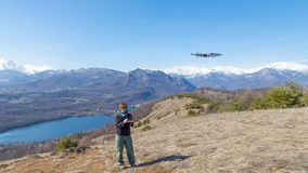 Bourdon de vol de femme dehors avec à télécommande Une personne dans le paysage scénique conduisant le pelliculage de bourdon pho Image stock