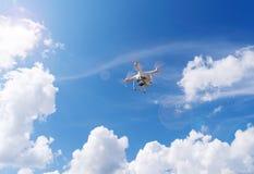 Bourdon de vol, quadcopter sur un fond de ciel bleu images stock