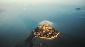 Bourdon pilotant très haut au-dessus du lever de soleil majestueux Mont Saint Michel, île irréelle de château entourée par marée  banque de vidéos