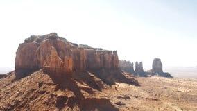 Bourdon tournant juste au-dessus du désert sec de grès près de la montagne rocheuse rouge incroyable et du ciel bleu en vallée de clips vidéos