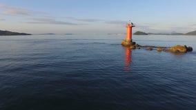 Bourdon volant au-dessus du bord de la mer avec le phare banque de vidéos
