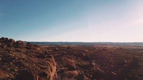 Bourdon volant bas au-dessus de la terre avec le paysage américain de grès couvert de roches et de pierres dans le coucher du sol banque de vidéos