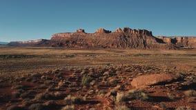 Bourdon volant bas au-dessus du désert de grès et du camion secs sur une petite route, horizon plat ensoleillé américain étonnant banque de vidéos