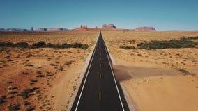Bourdon volant vers l'arrière au-dessus de la route vide iconique de désert de grès en vallée de monuments, Arizona avec de grand clips vidéos