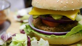 Bourdonnez dedans de hors focale sur l'hamburger fait à la maison avec des fritures sur la table en bois clips vidéos