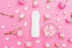 Bourgeon floraux de roses avec des pétales et shampooing sur le fond rose Concept de femelle de beauté Configuration plate, vue s Image libre de droits