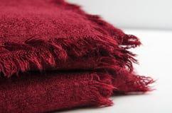 Bourgogne plié a tricoté le plaid sur le fond blanc Maison chaude et confortable photographie stock libre de droits