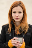 Cheerful smiling red-haired girl with cute smile red hot coffee. Royalty Free Stock Photos