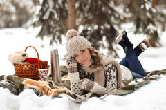 Happy,cute girl lay, relax on plaid in winter park Stock Images