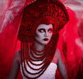 Wedding in red colors, bride in red veil, corona, red makeup and white linces,serious look,white long dress.Creative closeup portr Stock Images