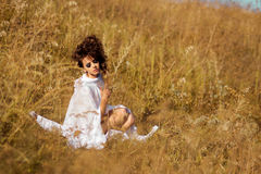 Seductive, beautiful fashionable model, girl with flowers sit in field Royalty Free Stock Images