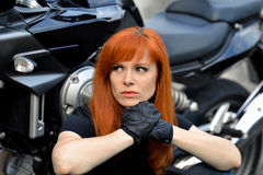 Curious,serious,red-haired girl with dangerous look with leather gloves and cool,modern bike,motorbike.Professional biker. Stock Photography