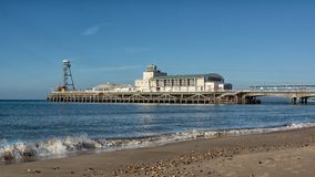 Bournemouth Pier. From a low angle showing breaking waves on the shore line and a deserted beach Stock Photos