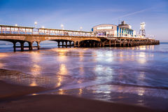 Bournemouth Pier at night Dorset. The lights of Bournemouth Pier at night reflected in the wet sand on the beach. Dorset  England UK Europe Royalty Free Stock Image