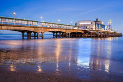 Bournemouth Pier at night Dorset. The lights of Bournemouth Pier at night reflected in the wet sand on the beach. Dorset  England UK Europe Stock Image