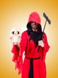 Bourreau dans le costume rouge avec la hache sur le blanc Photos stock