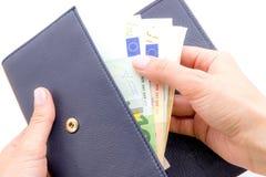 Bourse bleue avec des euros dans les mains sur le fond blanc Image stock