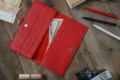 Bourse d'embrayage de bourse, accessoires de femme et argent rouges sur une table en bois blanche Image stock
