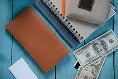 Bourse de Brown avec l'argent, le carnet et le businesscard sur la table bleue Photos stock