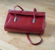 Bourse en cuir rouge - sac à main sur le bureau en bois photos stock