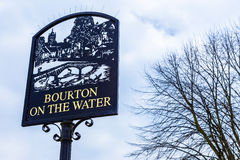 Bourton auf dem Wasser-Zeichen steht gegen bewölkten blauen Himmel Stockfotos