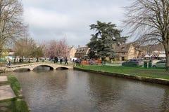 BOURTON-ON-THE-WATER, GLOUCESTERSHIRE/UK - 24 DE MARÇO: Turistas W Foto de Stock Royalty Free