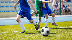 Bous play soccer match on sports field. Youth football league Stock Photos