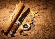 Boussole, couteau, pièce de monnaie et étoiles de mer sur de vieilles cartes de fond Image libre de droits