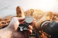 Boussole de prise de voyageur d'homme à disposition sur des jambes de fond en augmentant des bottes Fond brouillé photo stock