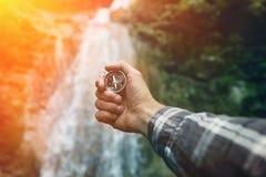 Boussole de Searching Direction With d'explorateur d'homme sur le fond de cascade, point de vue augmentant le concept de voyage d Photo libre de droits