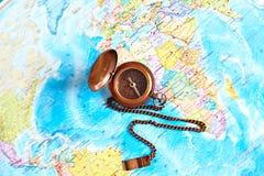 Boussole en laiton de vintage sur le fond de carte du monde Photographie stock