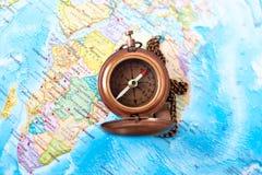 Boussole en laiton de vintage sur le fond de carte du monde Image stock