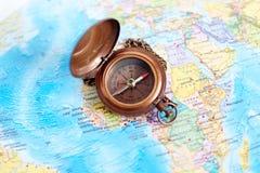 Boussole en laiton de vintage sur le fond de carte du monde Images stock