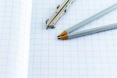 Boussole et crayon de rédaction sur le fond à carreaux Photos stock