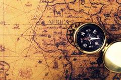 Boussole sur la vieille carte du monde de vintage avec l'espace de copie Photographie stock