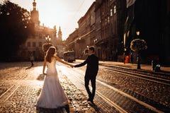 Bout droit de jeunes mariés leurs mains tout en marchant Photo libre de droits