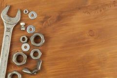 Bout en noot op een houten achtergrond Opzettende moersleutel Achtergrond met werkende hulpmiddelen Workshopmateriaal Royalty-vrije Stock Afbeeldingen