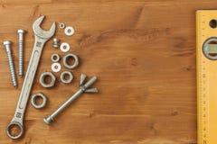 Bout en noot op een houten achtergrond Opzettende moersleutel Achtergrond met werkende hulpmiddelen Workshopmateriaal Royalty-vrije Stock Foto