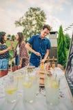 Bouteille à bière d'ouverture d'homme dans le barbecue d'été Images libres de droits