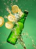 Bouteille à bière verte avec éclabousser le liquide photo libre de droits