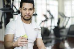 Bouteille asiatique de participation d'homme de l'eau après exercice dans le gymnase de forme physique images libres de droits