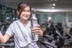 Bouteille asiatique saine d'exposition de prise de main de femme de l'eau de boissons avec le club de sport images stock