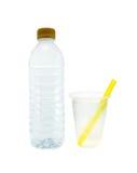 Bouteille avec des tasses de l'eau et de plastique d'isolement sur le blanc Photos libres de droits