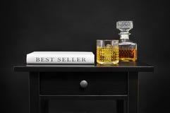 Bouteille avec la boisson alcoolisée et le livre avec le best-seller des textes Photographie stock
